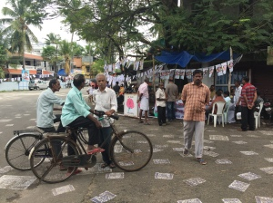 local election candidate station on a busy road with lots of people discussing the upcoming vote, in fort cochin, Kerala