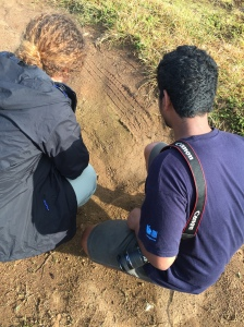 Catherine and Sachin looking at leopard tracks in the mud