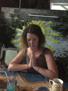 Catherine praying with an image of a halo behind her on a wall
