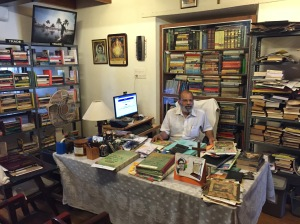 Mr Walton of Walton's homestay behind his desk surrounded by second hand books and helpful information about the local area