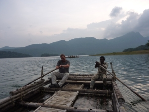 Rob rowing a large raft with another man across the Parambikulam Tiger Reserve reservoir